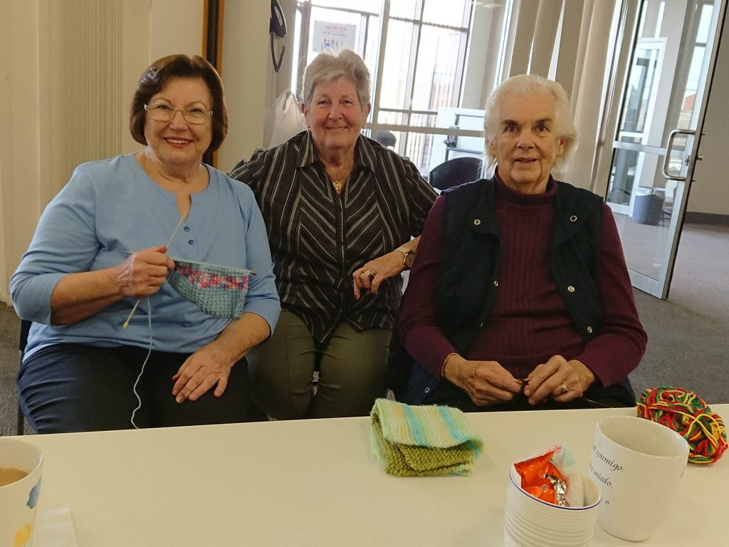 Three people at knitting group for older people run by The JNC