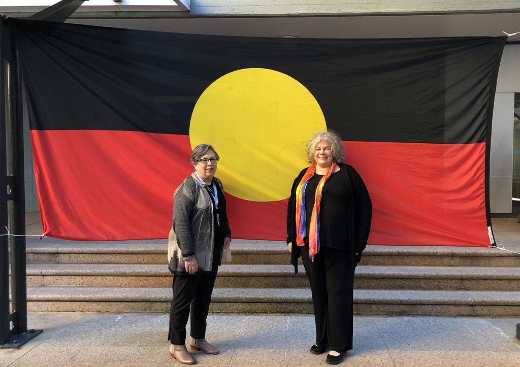 The Junction Neighbourhood Centre's Generla Manager, Janet Green, and Aboriginal Community Support worker, Barbara O'Neill, at the NAIDOC women's conference, standing in front of the Aboriginal flag