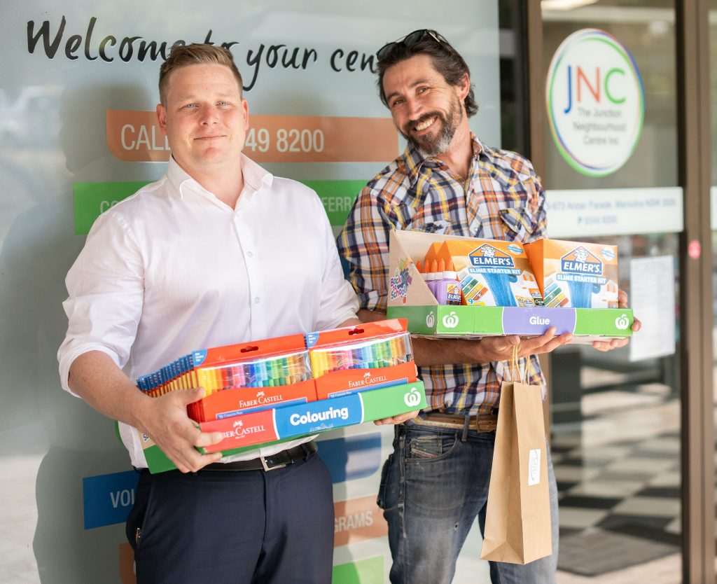 photo showing two men holding games and stationery for craft at 10th Family Fun Day in front of JNC office