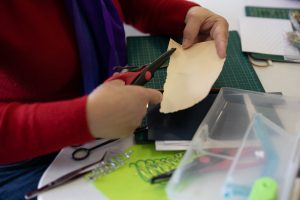 photo of hands cutting out paper in one of JNC's groups and classes for older people