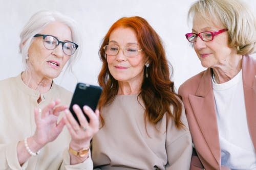 photo of three women with a mobile phone to illustrate what's on at JNC